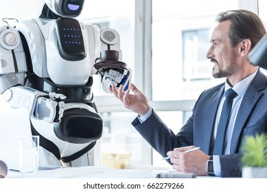 Droid is bringing coffee for pleasant businessman