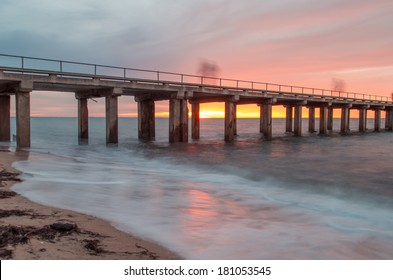 Dromana Pier on the Mornington Peninsula, near Melbourne Australia, at sunset.  The photo is a long second exposure and the figures on the pier appear ghostly.