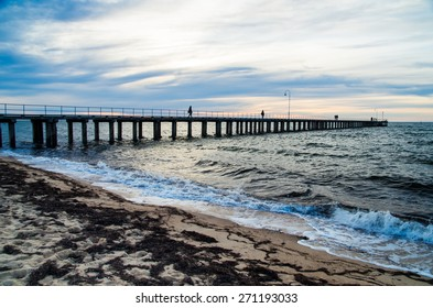 Dromana Pier on the Mornington Peninsula, south-east of Melbourne, Australia, juts into Port Phillip Bay. The image was taken close to sunset. Unidentifiable people are seen as silhouettes on the pier