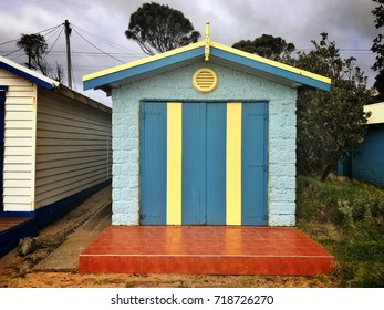 Dromana Public Foreshore bathing box, pale blue with a striped yellow and turquoise door