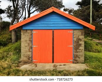 Dromana Public Foreshore bathing box with orange doors and blue fascia boards