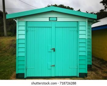 Dromana Public Foreshore bathing box painted aqua, against a stormy sky
