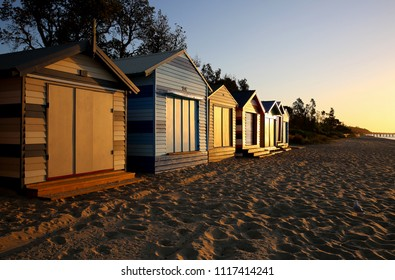 DROMANA, VICTORIA, AUSTRALIA - 10 FEBRUARY 2016: Iconic bathing boxes on Melbourne's Mornington Peninsula basking in the warm glow of a golden sunset.