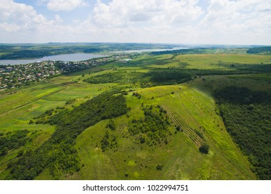 dron view on forest and green fields with villade at lake