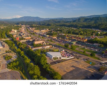 Drone, aerial, angled view of main strip, attractions, and mountains in Pigeon Forge, Tennessee