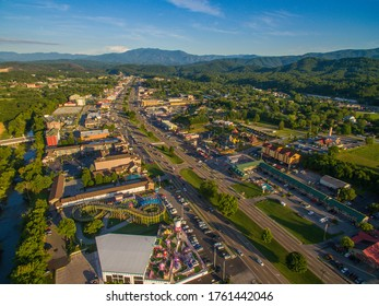 Drone, aerial, angled view of shadows cast from setting sun on main strip in Pigeon Forge, Tennessee