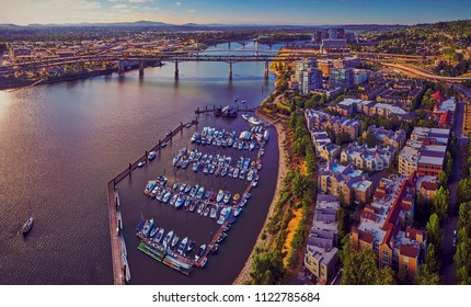 Drone aerial of Downtown Portland at Tom McCall Waterfront Park overlooking the Marina on early sunny morning with Tilikum Crossing Bridge in the distance