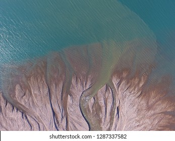 Drone aerial image of murky glacial melt water entering a fjord in northeast Greenland at a coastal delta