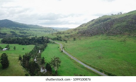 Drone aerial photo above countryside meadow with road valleys mountains green grass blue sky and tall trees