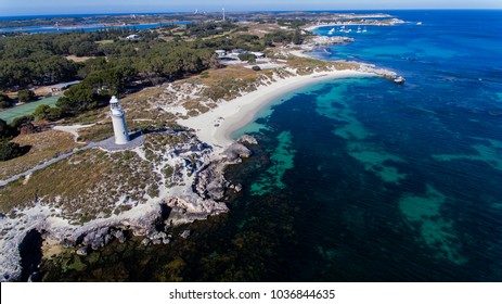 Drone aerial photo of the lighthouse and Pinkies Beach and The Basin next to the ocean, water and reef with the salt lakes in the distance on Rottnest Island, Western Australia