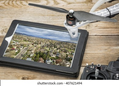 drone aerial photography concept - reviewing aerial picture of residential area on a digital tablet with a drone rotor and radio control transmitter,