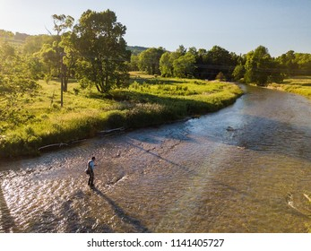 Drone aerial shot of a man fly fishing in the summer in a river