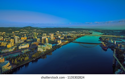 Drone aerial sunrise panorama of Portland waterfront with a ship loading cargo and the Fremont Bridge reflecting off the Willamette River