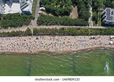 Drone aerial top down view on sunny beach with sunbathers with windbreaks and towels at sea in touristic city.