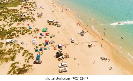 Drone aerial view of the camping on the sand beach with turquoise sea. Aerial view of the Sandy spit with many tents on the beach. Camping at summer beach.