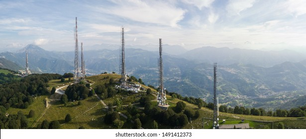 Drone aerial view of a group of towers for telecommunications, television broadcast, cellphone, radio and satellite on Linzone mountain peak. Electromagnetic and environmental pollution. Italian Alps