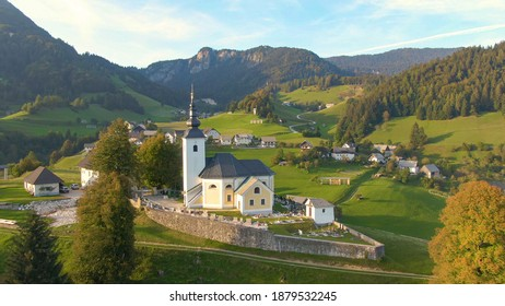 DRONE: Aerial view of the idyllic Slovenian countryside on a sunny autumn evening. Flying around a church and cemetery on top of a grassy hill overlooking the idyllic countryside in Soriska Planina.