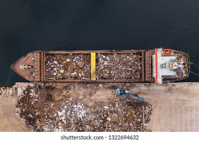 Drone aerial view loading in ship holds scrap metal for transportation. Collection of metal for secondary raw materials. Metallic trash for recycling. Black scrap, color scrap. Scrap import and export