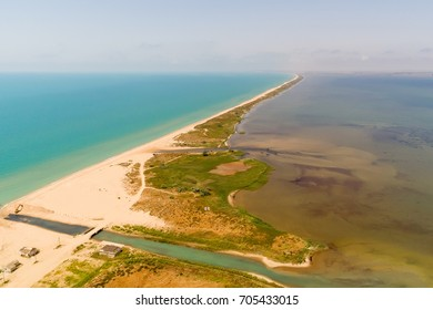 Drone aerial view of the long sand spit separates the sea with camping on the beach. Aerial view of the Sandy spit dividing the water of two colors. Sea and liman, firth at Russian south.