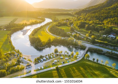 Drone aerial view of Rauma river and the mountain peaks in backgroud. Summer sunset in Norway