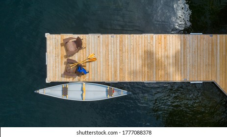 Drone aerial view of two Adirondack chairs on a wooden dock facing the blue water of a lake in Ontario. A yellow canoe is tied to the dock. Life jacket and oars are visible near the chairs.