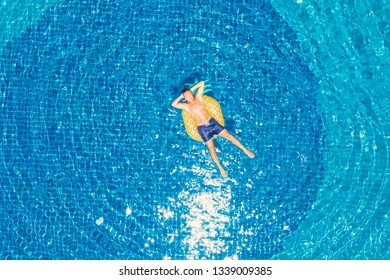 Drone aerial view of Young man floating on inflatable pineapple over blue swimming pool enjoying sunbathing and vacations in tropical destination. People travel tourism holidays concept