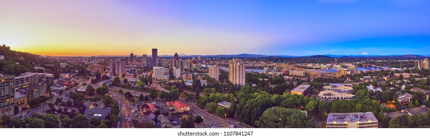 Drone aerial wide panorama on a summer evening near sunset of downtown Portland with the Ross Island, Tilikum, Freeway, Hawthorne and Morrison with Mt St Helens and Mt Hood in the distance