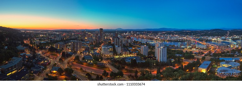 Drone aerial wide panorama on a summer evening at twilight of downtown Portland with the Tilikum, Freeway, Hawthorne, and Morrison bridges in view with Mt St Helens in the distance