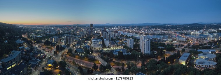 Drone aerial wide panorama on a summer evening at twilight of downtown Portland with the Freeway, Hawthorne, and Morrison bridges in view with Mt St Helens