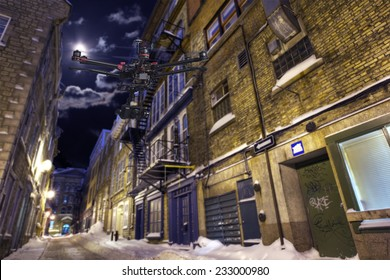 A drone with a camera is flying along a deserted street in a winter night.