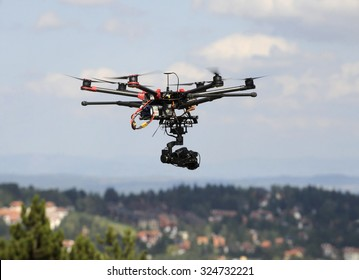 A drone with a camera flying high above a residential area filming