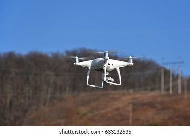 A drone with a camera flying over land.  Drones are a popular tool used for aerial photography.