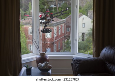 A drone with a camera hovering outside living-room window