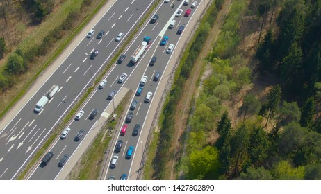 DRONE: Cars driving along congested entry lane and joining the dense highway traffic. Flying above an entry lane leading rush hour traffic to a two lane freeway. Cars and trucks fill up the motorway.