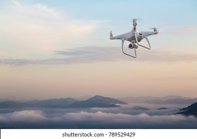 drone copter flying with digital camera.Drone with high resolution digital camera. Flying camera take a photo and video.The drone with professional camera takes pictures of the misty mountains.