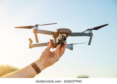 drone copter in hand on sky background. Remote controlled copter with digital camera in the hand. Closeup. New tool for aerial photo and video.
