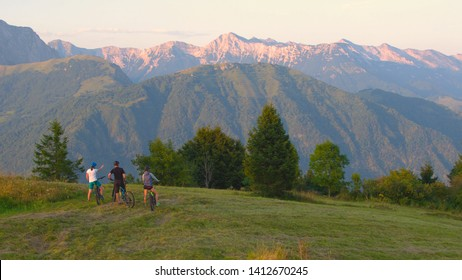 DRONE COPY SPACE: Fit friends plan their route for a scenic mountain biking trip on a sunny morning. Young tourists on ebikes look around the scenic summer evening nature after fun journey in Slovenia