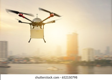 Drone delivery flying carry product paper box on city sunset sky
