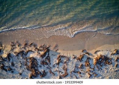 Drone field of view of water meeting beach in Mandurah, Western Australia.