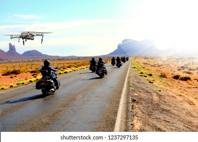 Drone filming motor biker on the road, in Monument Valley