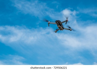 Drone in flight in blue sky with white cloud