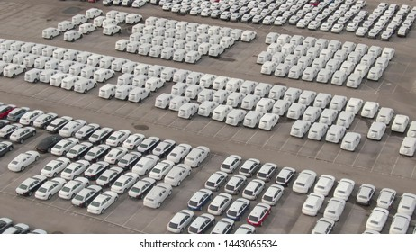 DRONE: Flying above a car park reserved for brand new cars coming in from a nearby port. Countless cars wrapped in white paper are neatly organized in a massive parking lot for imported vehicles.