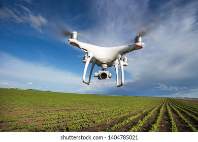 Drone flying above soybeanr field in spring with blue sky and white clouds in background