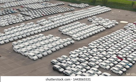 DRONE: Flying above a storage car park reserved for brand new imported cars. Countless cars wrapped in white paper are neatly organized in a massive parking lot serving as storage for car dealership.