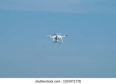 Drone flying against the blue sky, quadcopter in the sky, white quadcopter shoots,