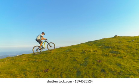 DRONE: Flying along an athletic man pedalling an e-bike up a steep grassy hill. Male tourist downhill biking in the Slovenian mountains riding his electric bicycle uphill on a sunny summer day.
