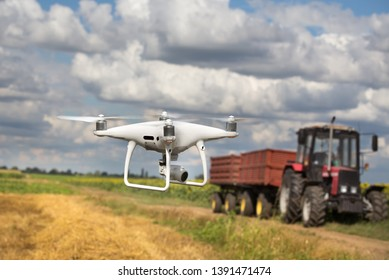Drone flying in front of tractor with trailer in field in early summer. Technology innovation in agriculture