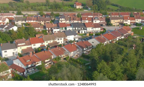 DRONE: Flying high above luxury terraced houses and the empty asphalt road running through the tranquil suburbs. Beautiful green nature surrounds the idyllic middle class suburbia in sunny Slovenia.