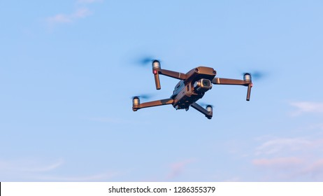 Drone flying over landscape. UAV drone copter flying with digital camera. Drone flying overhead in cloudy blue sky. Quad copter is flying over the  field.