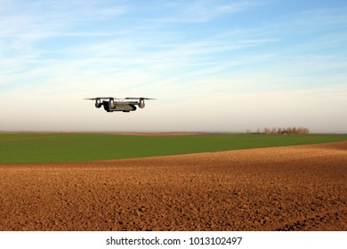 The drone is flying over the plowed field